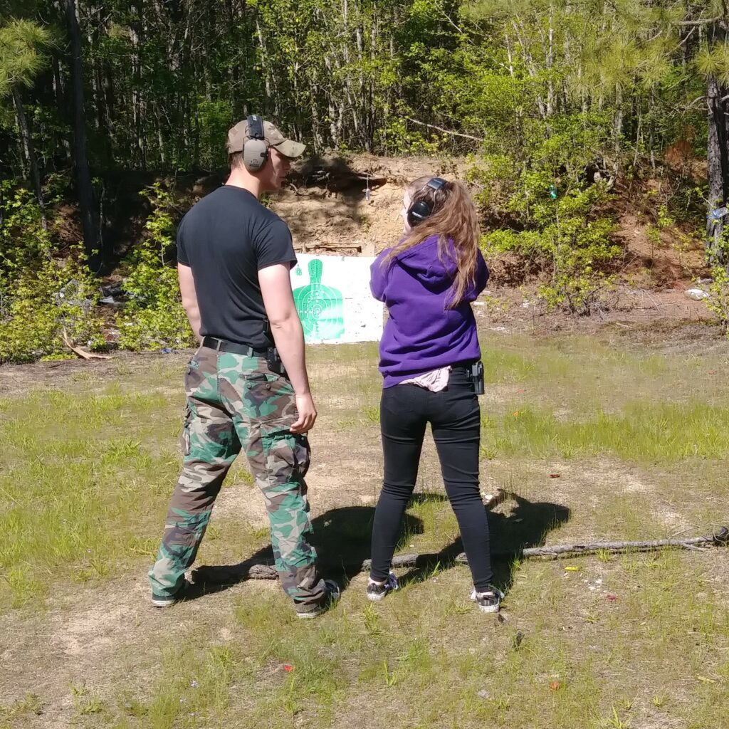 A young shooter trying out first guns with an instructor at the range