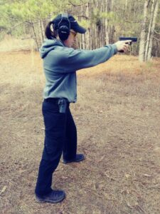 Demonstrating the modern isosceles stance with a pistol at a shooting range