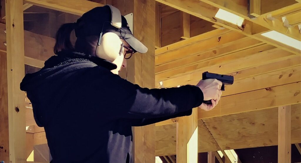 The author firing a pistol at the shooting range.
