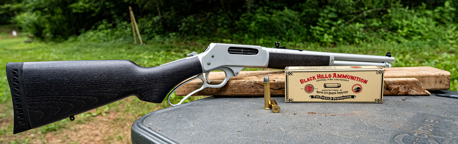 45-70 lever action rifle with ammo on a shooting bench