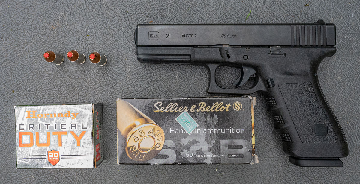45 ACP ammo and a Glock pistol on a shooting bench