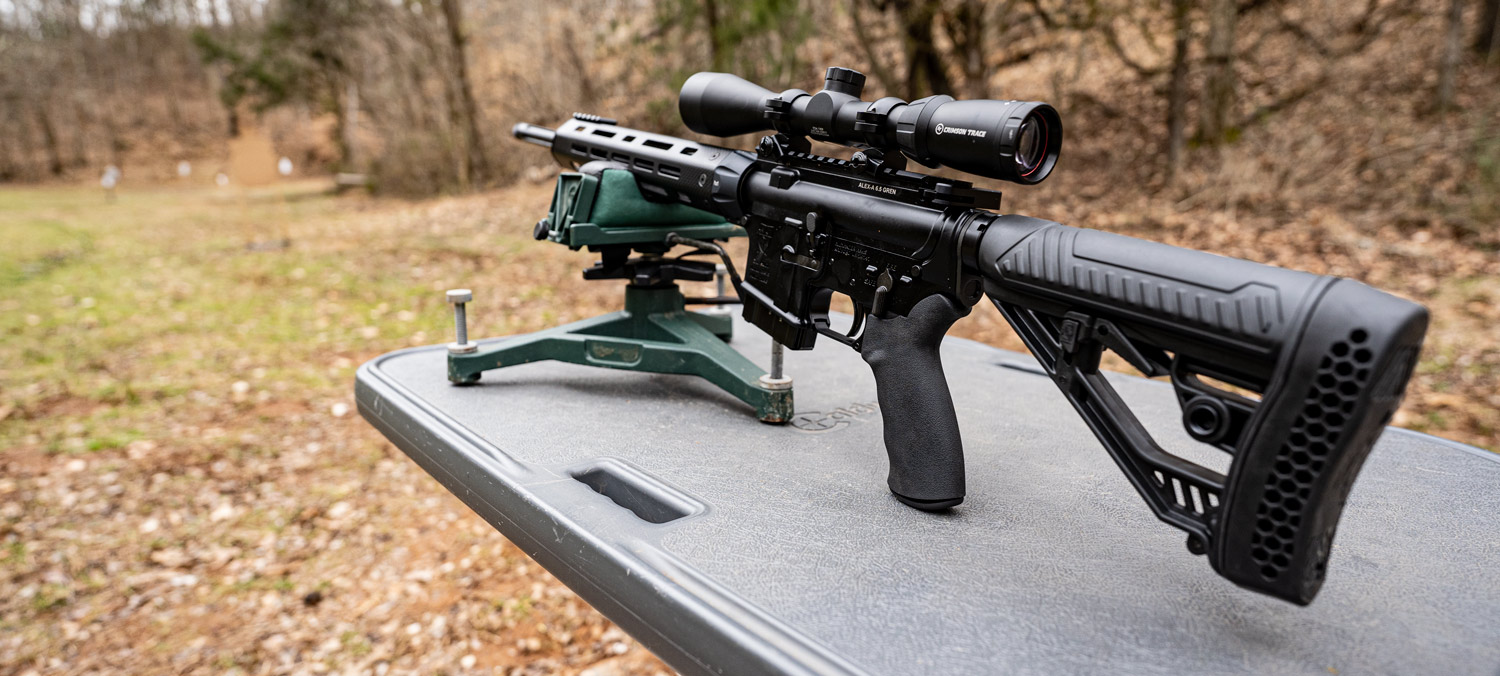 A 6.5 Grendel rifle equipped with an MOA optic on a benchers
