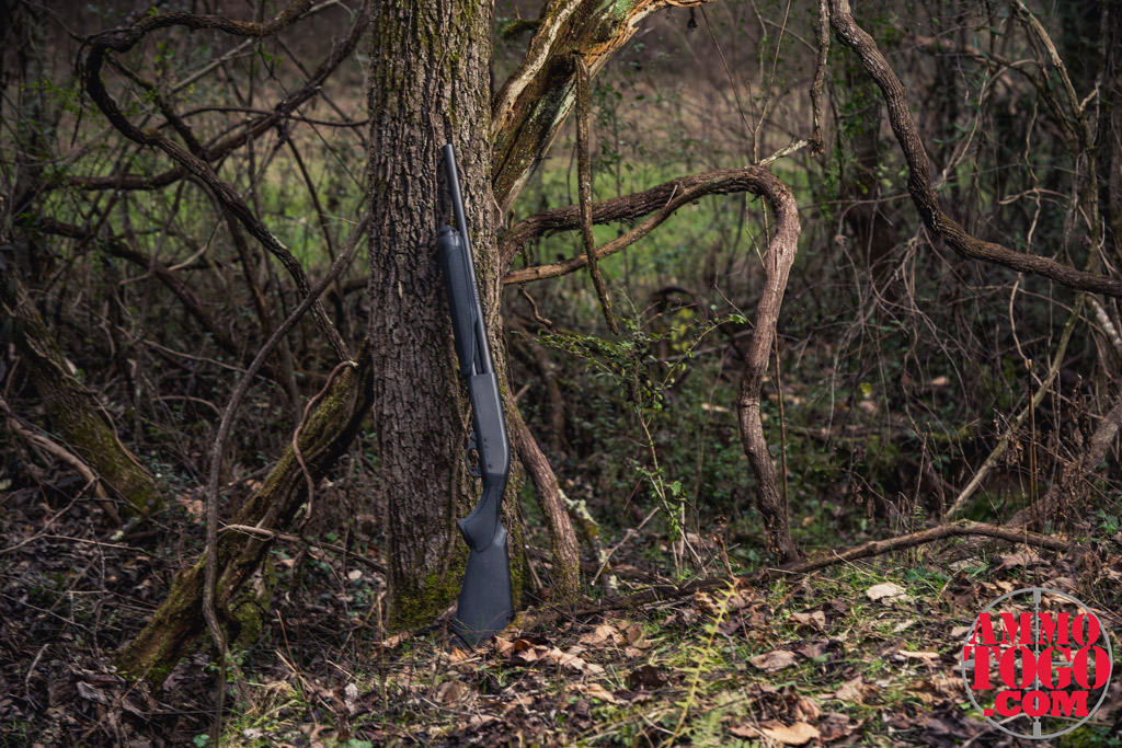 a photo of a 12 gauge remington 870 against a tree outdoors