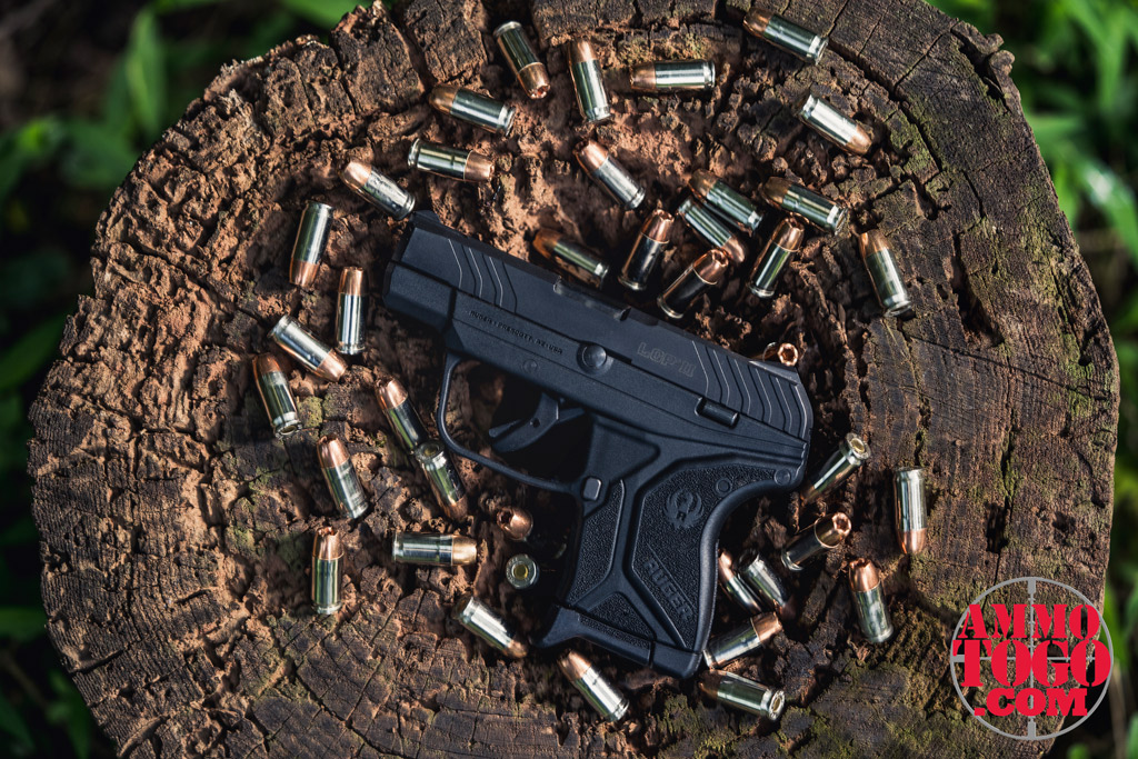 photo of ruger LCP 380 handgun with 9mm bullets on a tree stump