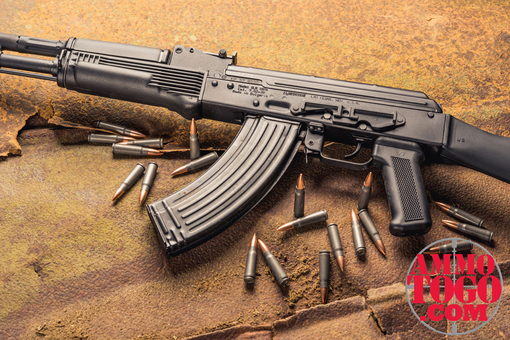 photo of an AK47 on rusty metal with ammo