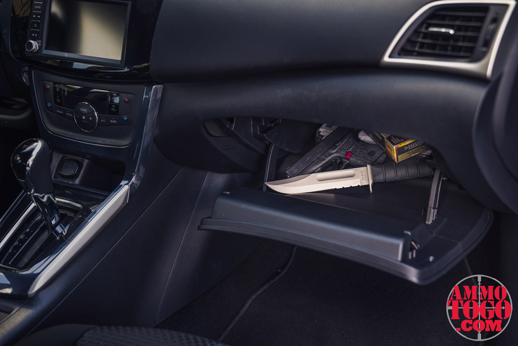 A photo of a 9mm glock 43 and a kabar knife in a glove compartment showing gun laws vs knife laws