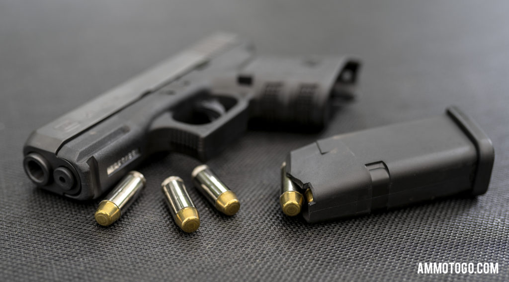 Glock 29 sitting on a table with 10mm ammunition and magazine unloaded