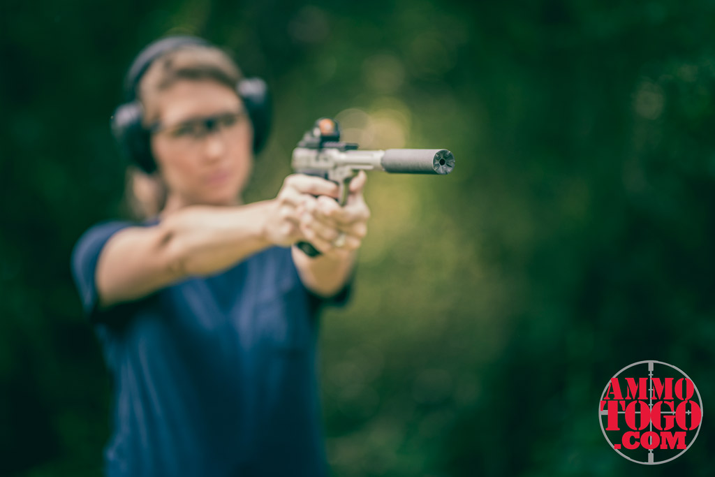 a photo of a woman shooting while pregnant outdoors with a suppressed 22 pistol