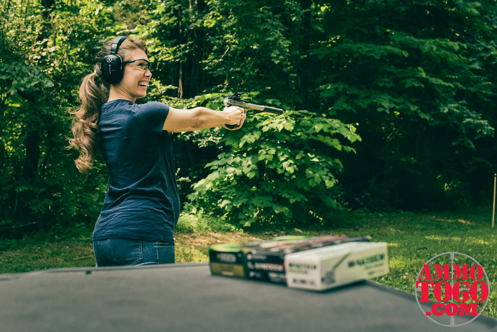 Pregnant woman shooting a pistol at an outdoor shooting range