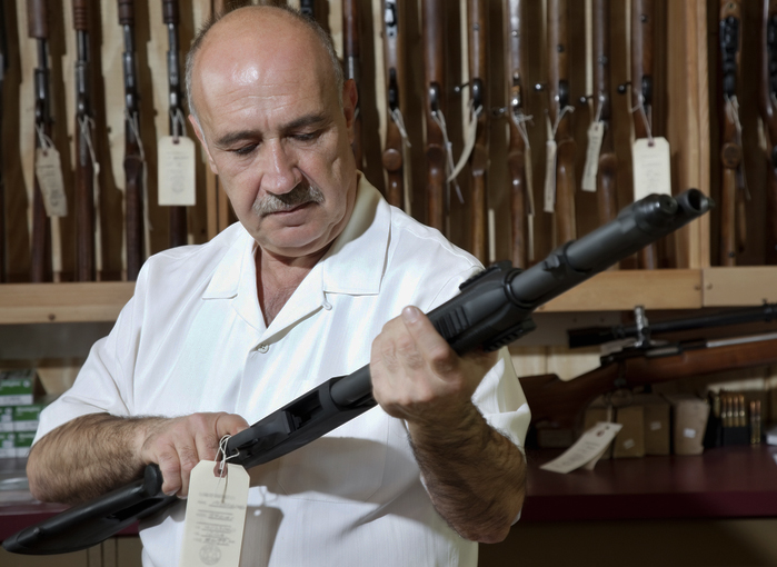 A Federal Firearms Licensee in his shop with a shotgun