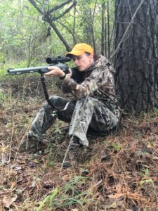A hunter using a muzzleloader in the woods