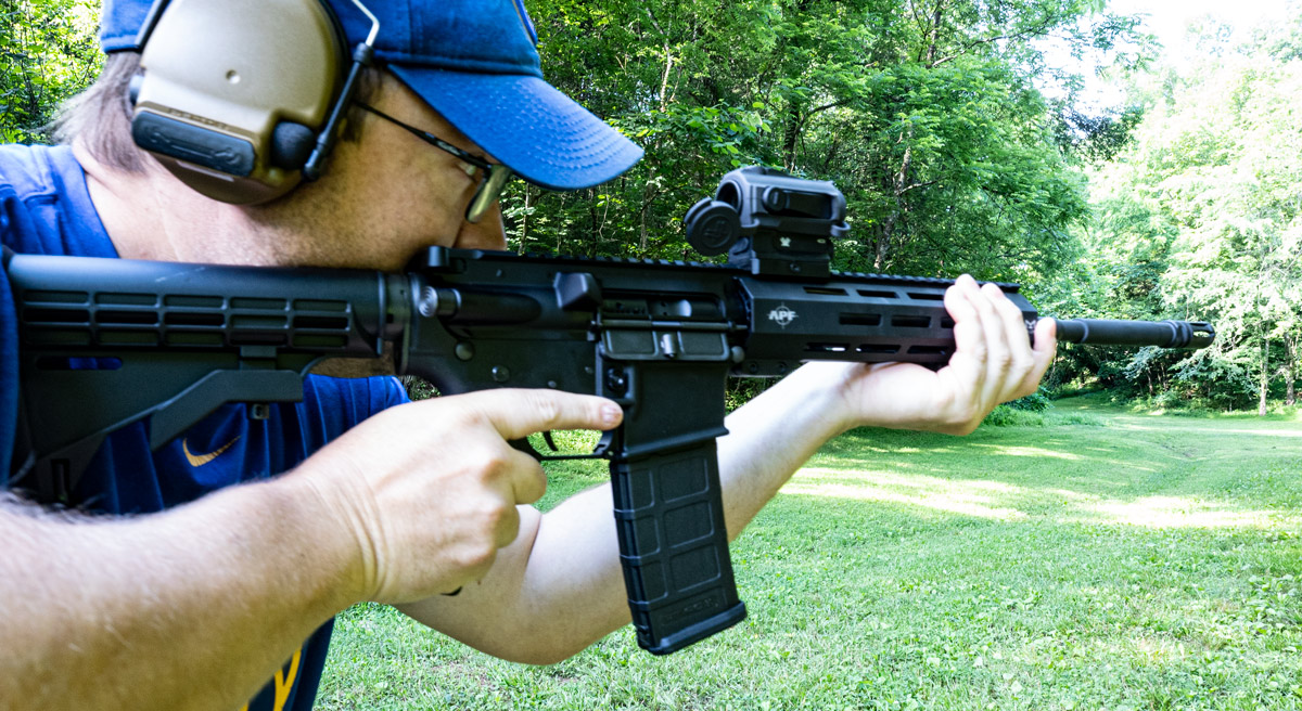 A shooter at the range with an AR15 firing rounds.
