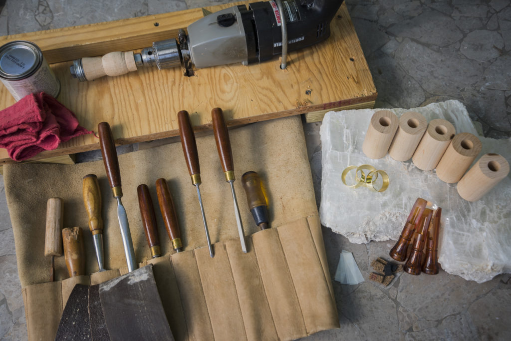 The different pieces needed to make a duck call on a workshop table
