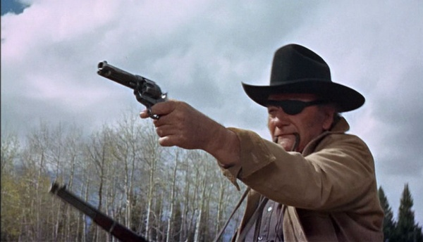 John Wayne Played Rooster Cogburn and fired several guns in the movie True Grit