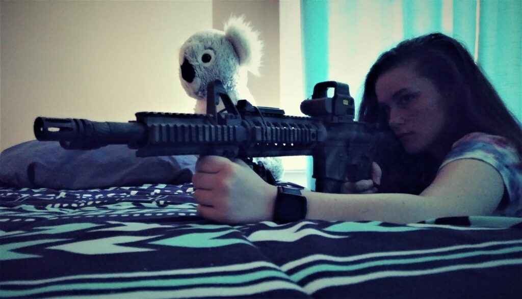 A young girl with an AR-15 rifle behind a bed