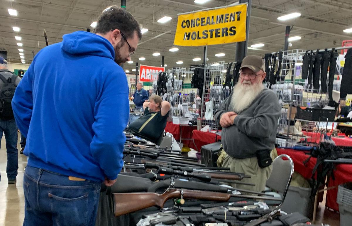 man considering a gun purchase at a gun show