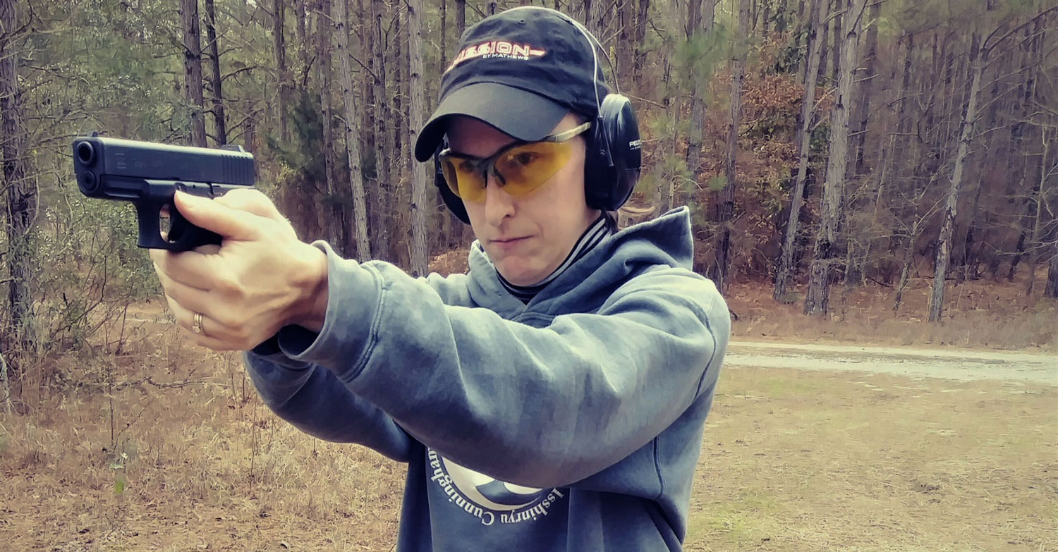The author demonstrating proper pistol shooting stance at the shooting range
