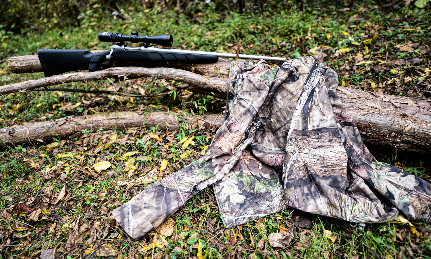 scent control hunting jacket and rifle in the woods