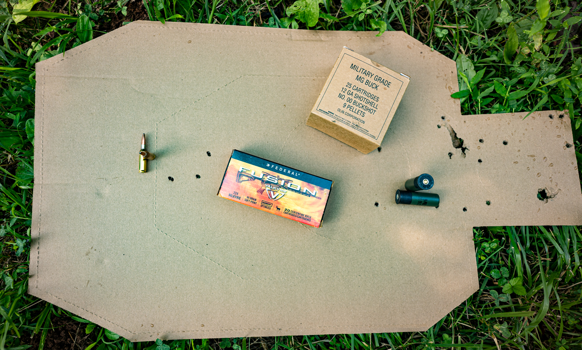 A cardboard target shot with both rifle and shotgun ammo