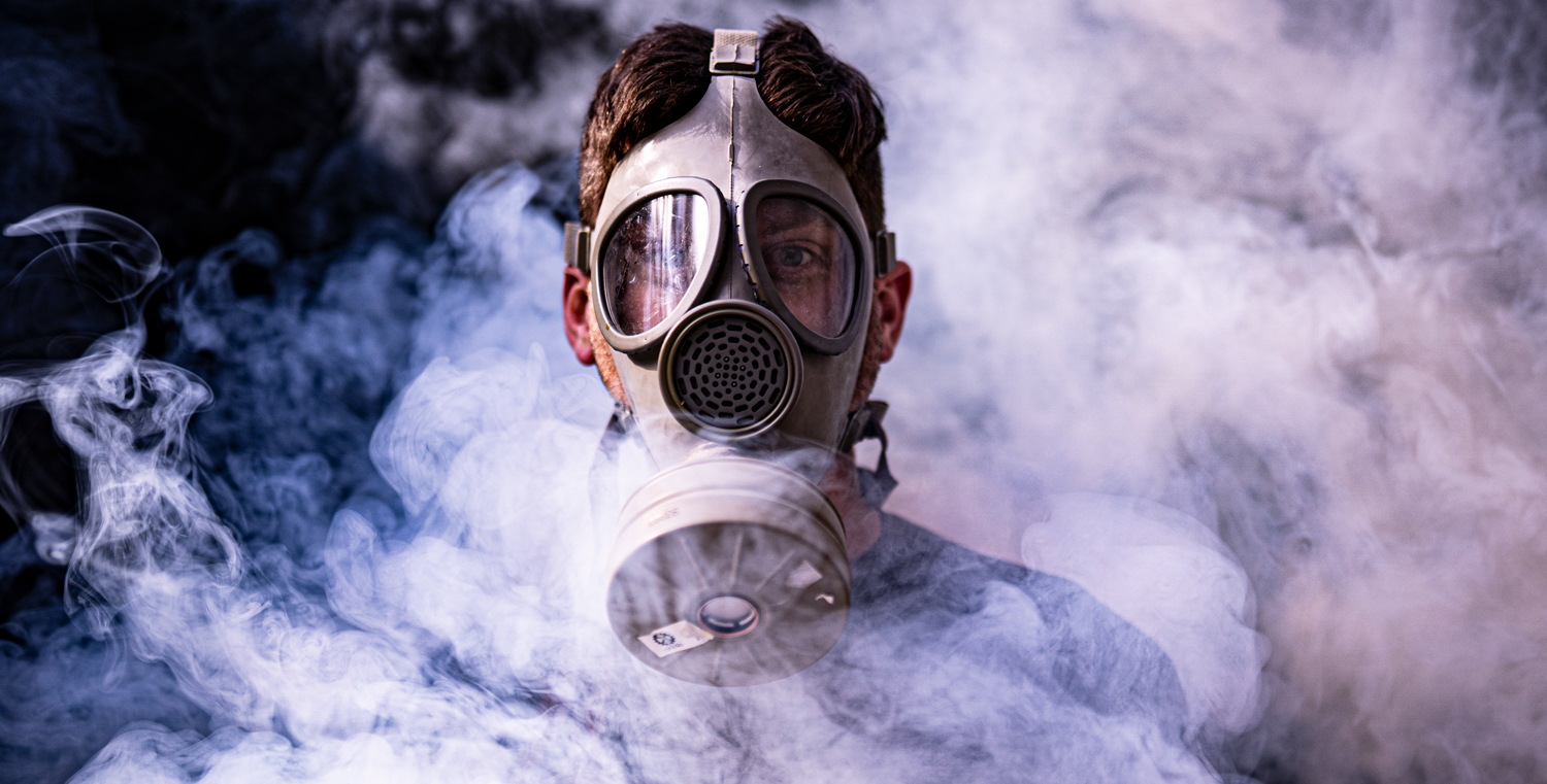 author wearing a gas mask amid a smoke field