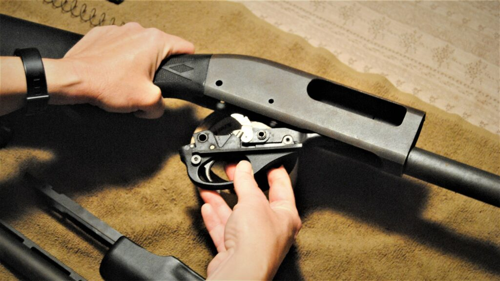 Removing the trigger group in order to clean the chamber area of the shotgun